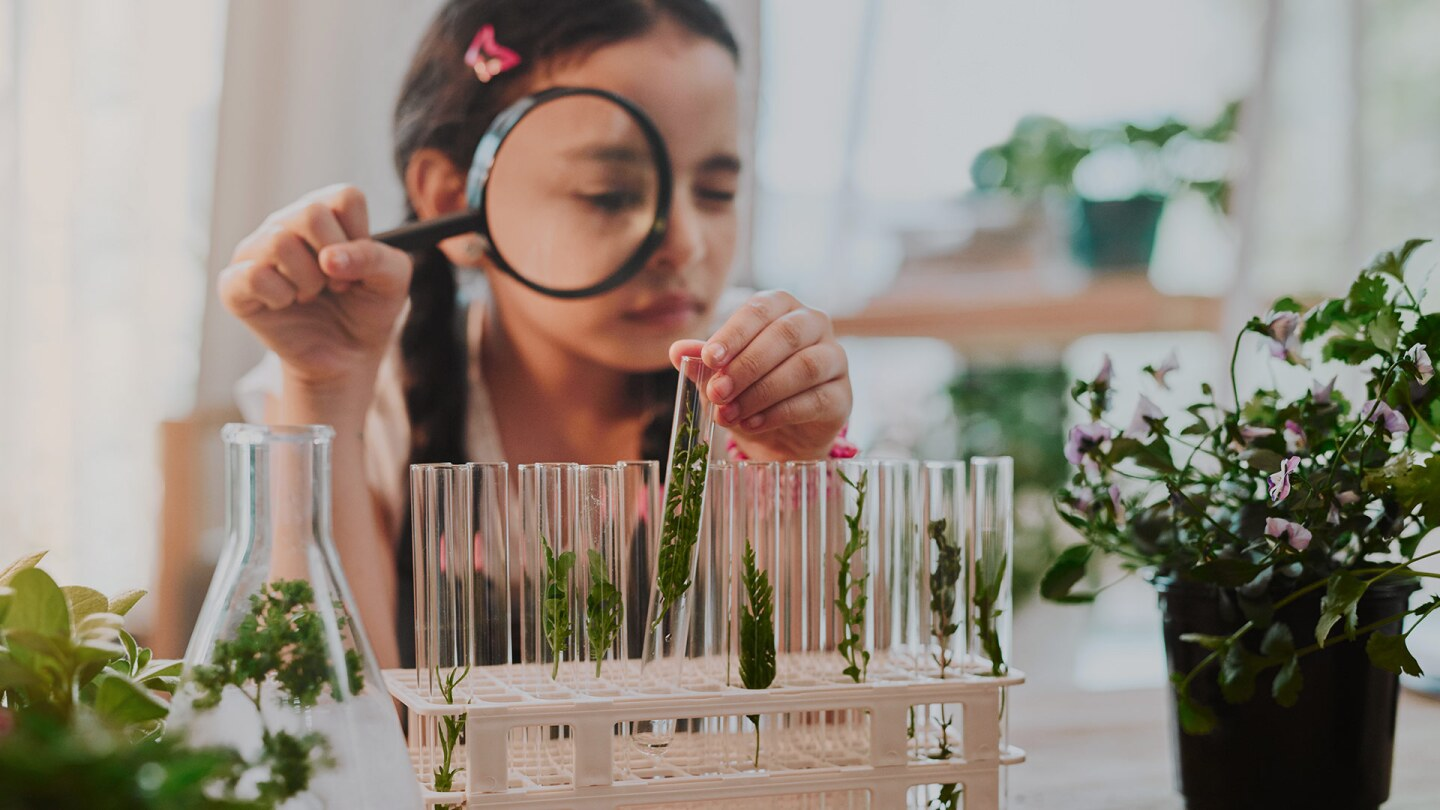 A little girl looks at test tubes through a magnifying glass. iStock