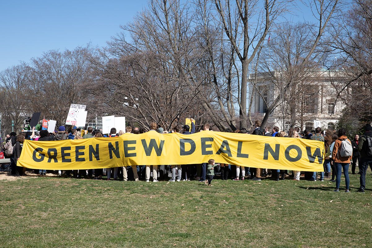 """Activist outside the Congress demanding a vote to pass """"The Green New Deal."""" 