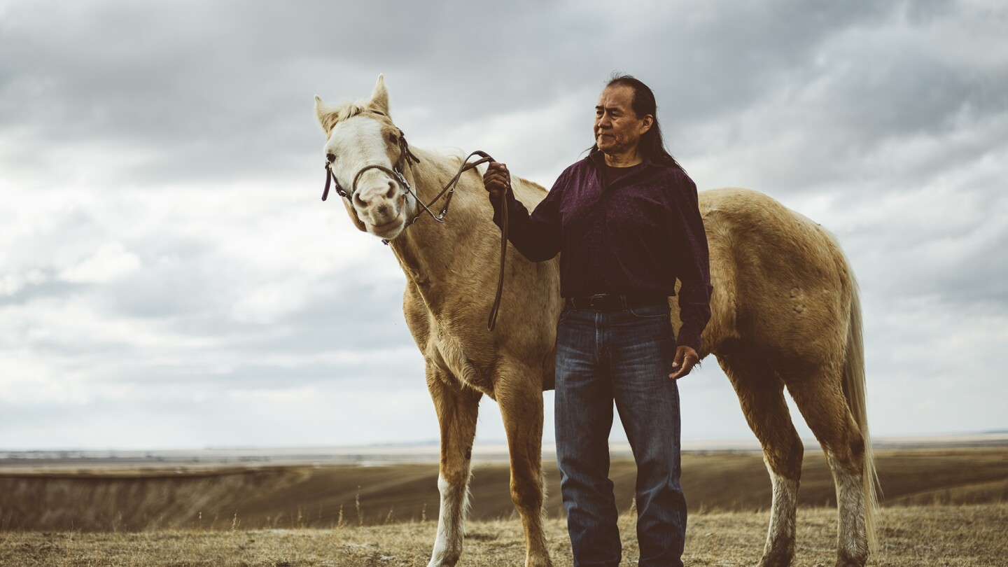 A man standing beside a horse, holding its reins in his hand.