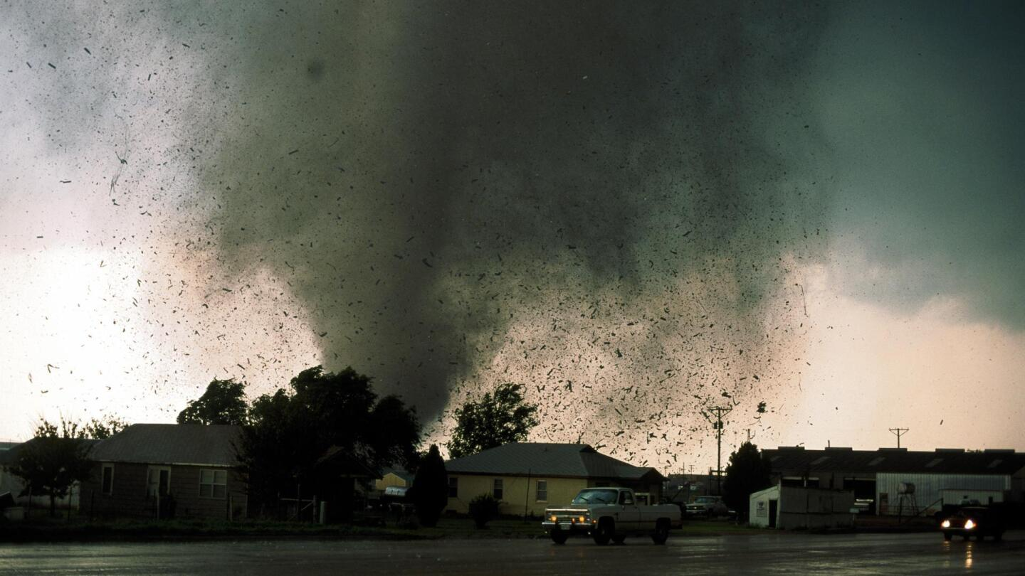 """A small suburban street with a raging tornado not too far in the distance behind it. 
