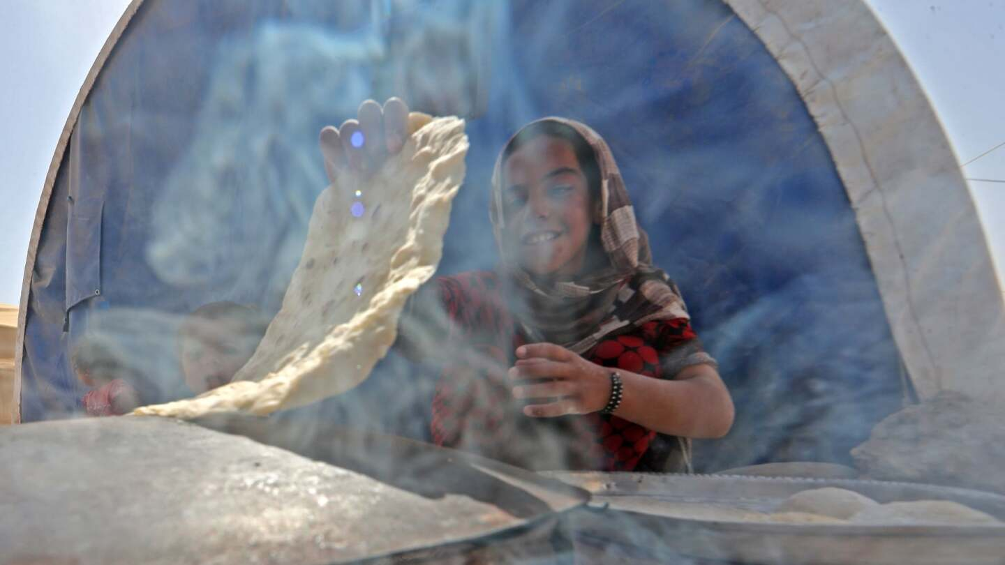 A displaced Iraqi girl bakes bread at the Hammam al-Alil camp for internally displaced people south of Mosul on May 26, 2017. | Karim Sahib/AFP/Getty Images