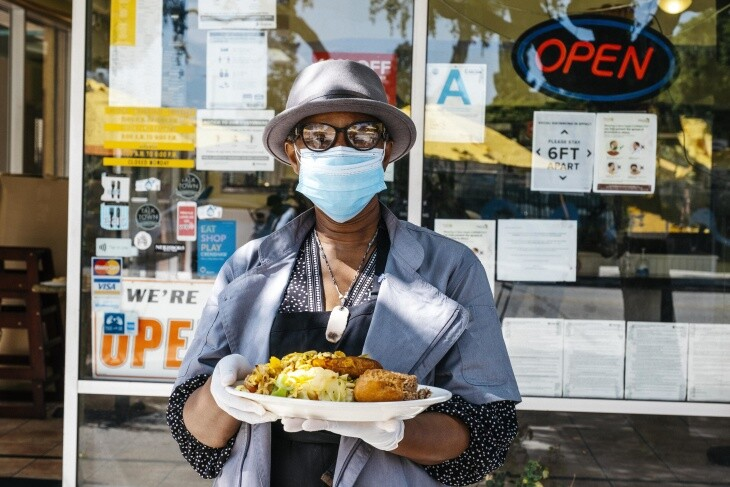 Marlene Beckford poses outside of Ackee Bamboo, holding one of her restaurant's signature dishes, ackee and saltfish.