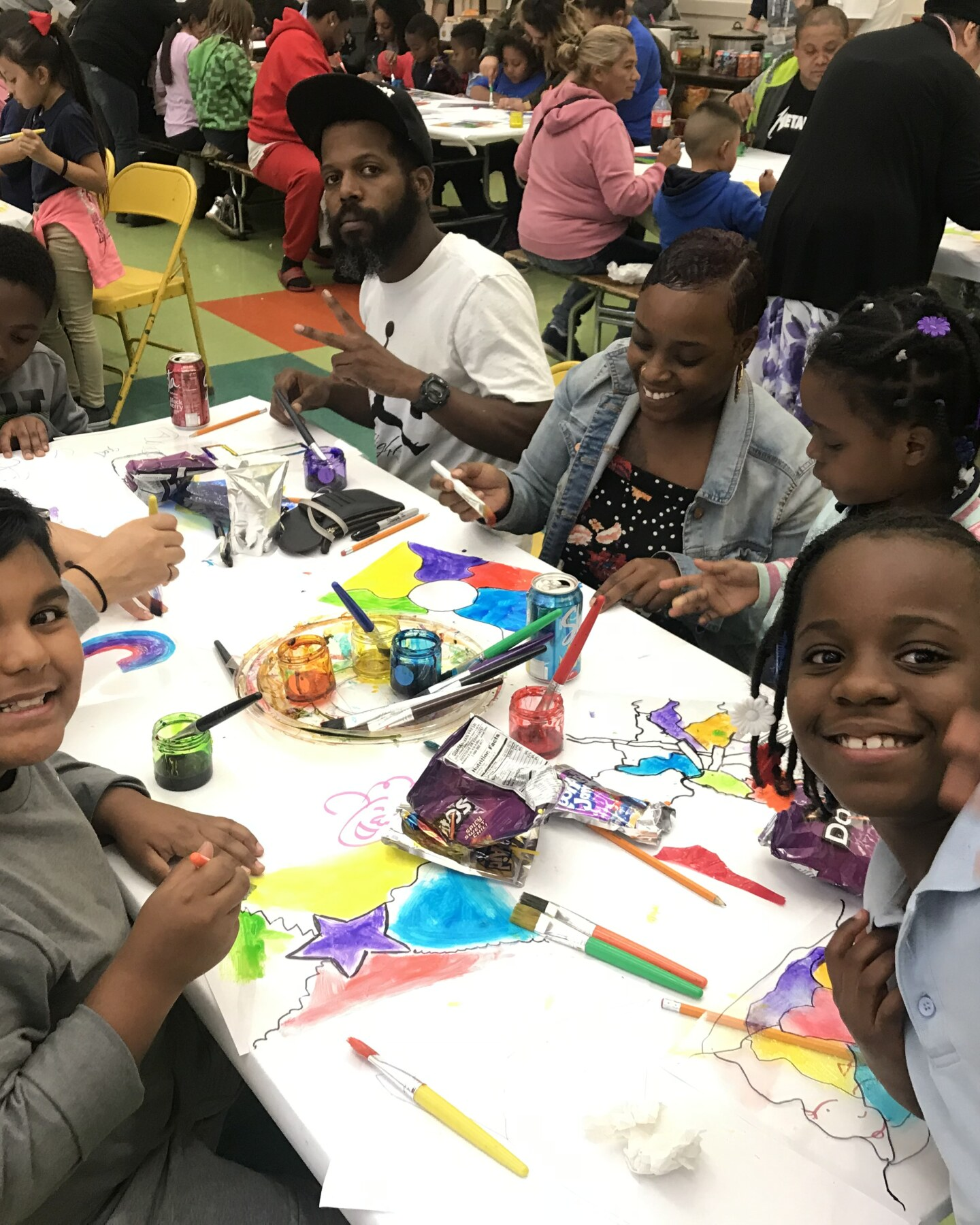 Children and their parents from Compton's McKinley K-8 School of Integrated Arts smile at the camera while doing arts and crafts activities.