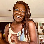 A Black woman (Sarafina Arthur-Williams) wearing glasses and a sleeveless blouse smiles at the camera