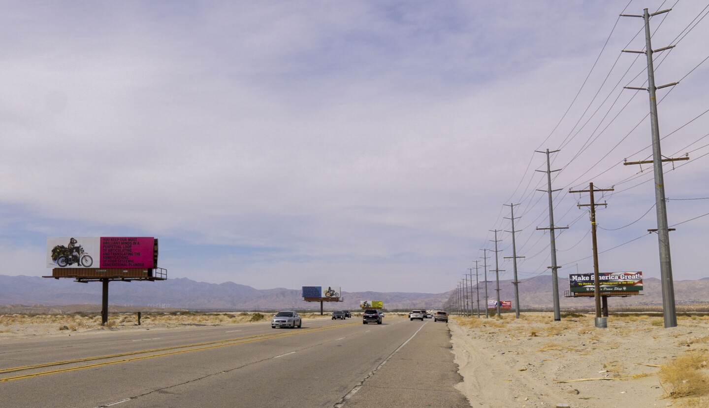"""Simmons' """"Because You Know Ultimately We Will Band a Militia"""" billboard art installation stands opposite of a billboard advertisement for Rocky's Pawn Shop. Behind the billboards is a clear, landscape view of the desert. Cars drive on the road that separates the installation and advertisement."""