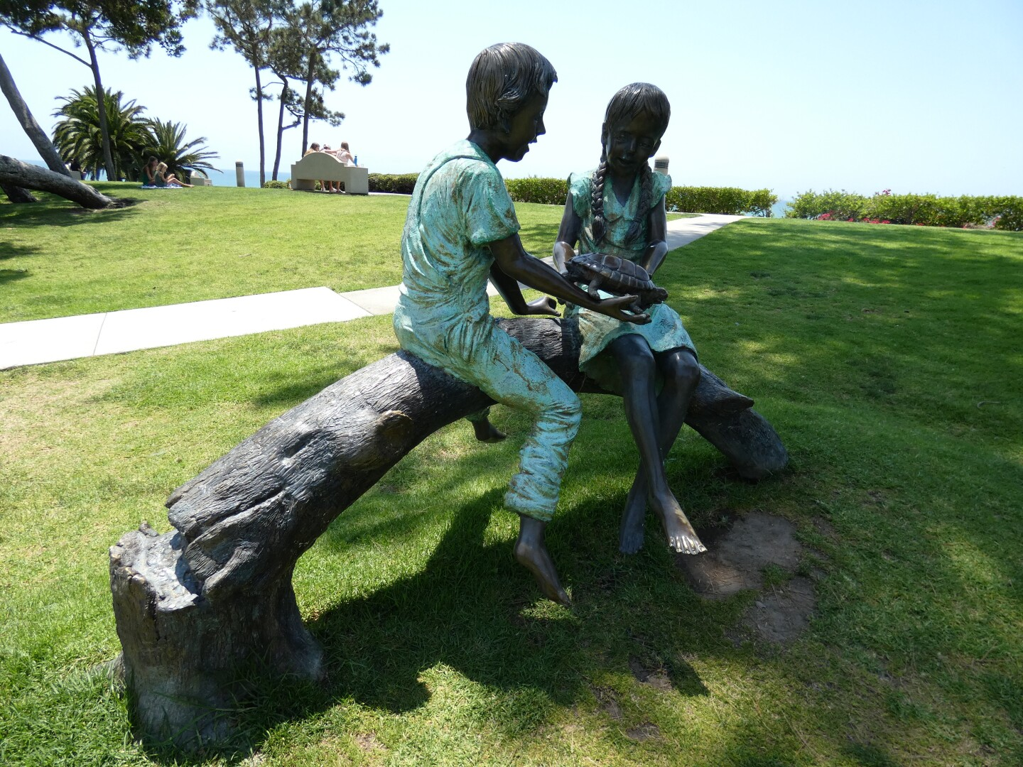 A bronze sculpture depicts two children sitting on a log is planted under a shaded patch of grass at Pines Park. The children look at a turtle held by one of the them. Their clothing is a bright, teal-green.