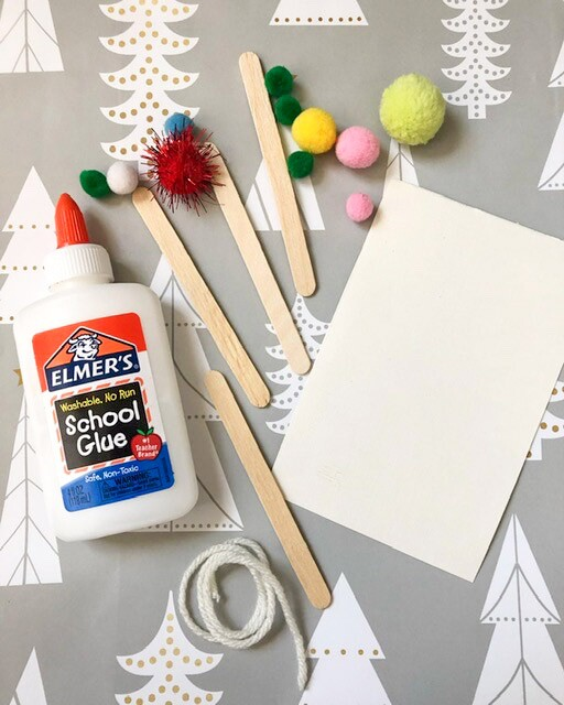 A tube of glue, popsicle sticks, colorful pom poms, a piece of string and a piece of paper are laid out on a table.