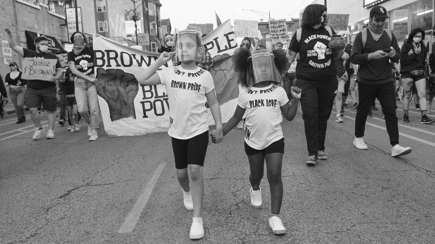 "Young girls wearing ""Brown Pride"" and ""Black Love"" T-shirts hold hands during a march. 