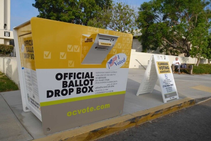 Drive-through ballot drop-off boxes and COVID-19 safety signs outside the Orange Country Registrar. | Chava Sanchez/LAist