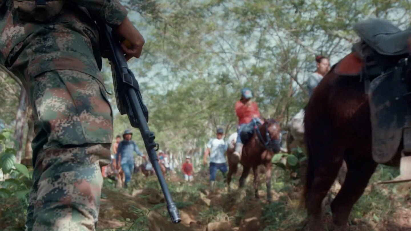 A soldier holding a rifle supervises a line of people traversing by.
