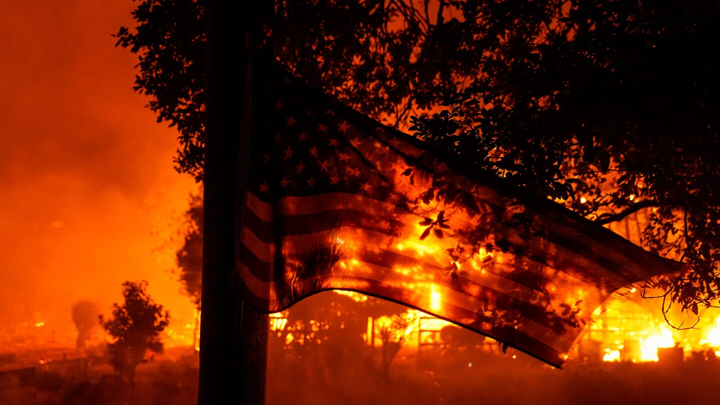 A U.S. Flag flaps in the wind as the Shady Fire impacts structures along CA-12 on Monday, Sept. 28, 2020 in Santa Rosa, California. | Kent Nishimura/Los Angeles Times via Getty Images