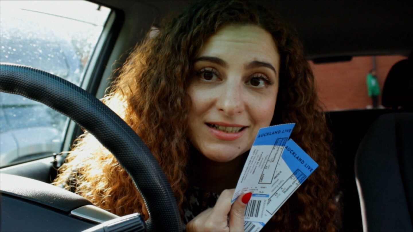 "Lily Siddawi holding tickets behind a steering wheel. | Still from ""Both Worlds"""
