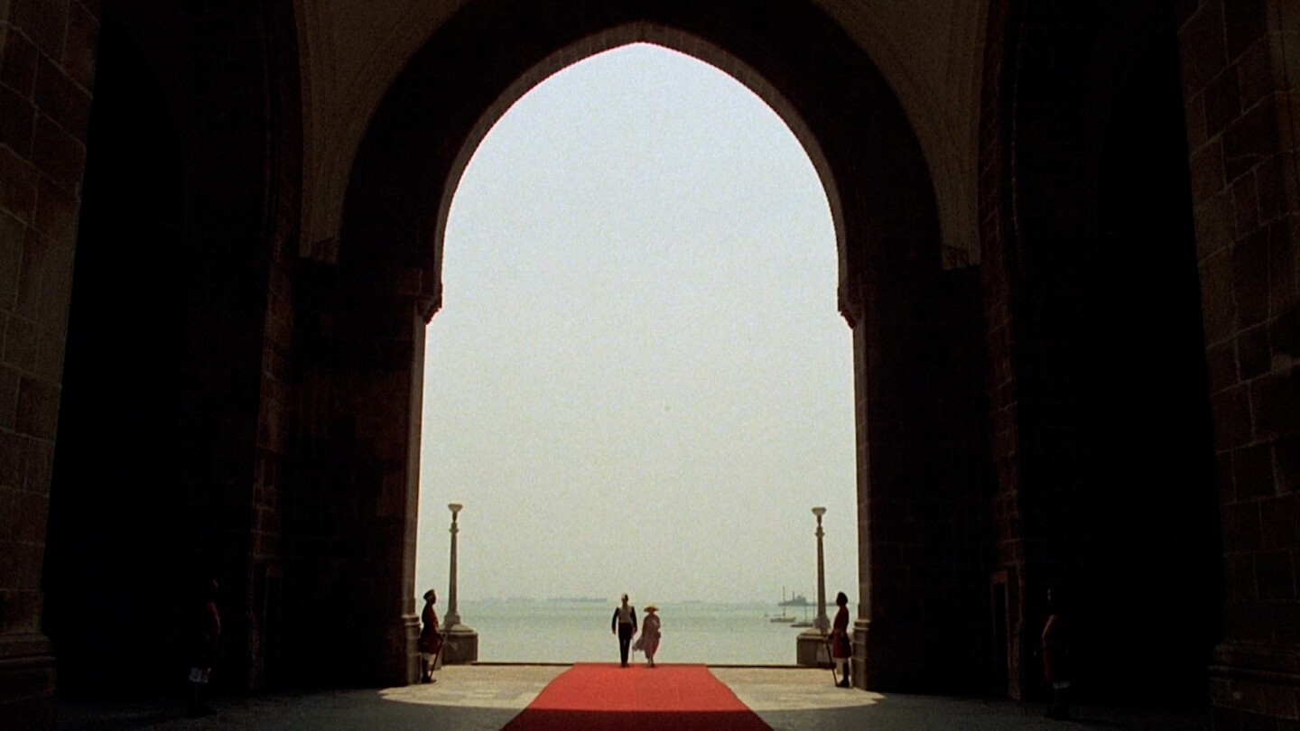 "Two people walking through a high, arched entrance with two guards standing by. | From ""The Passage to India"""
