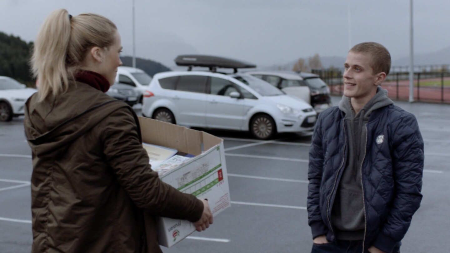 """Helena talks to someone while holding a box from """"Home Ground: The Great Escape."""""""