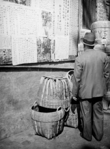 A Chinatown resident reads a billboard of papers written in Chinese.   Courtesy of the Los Angeles Public Library