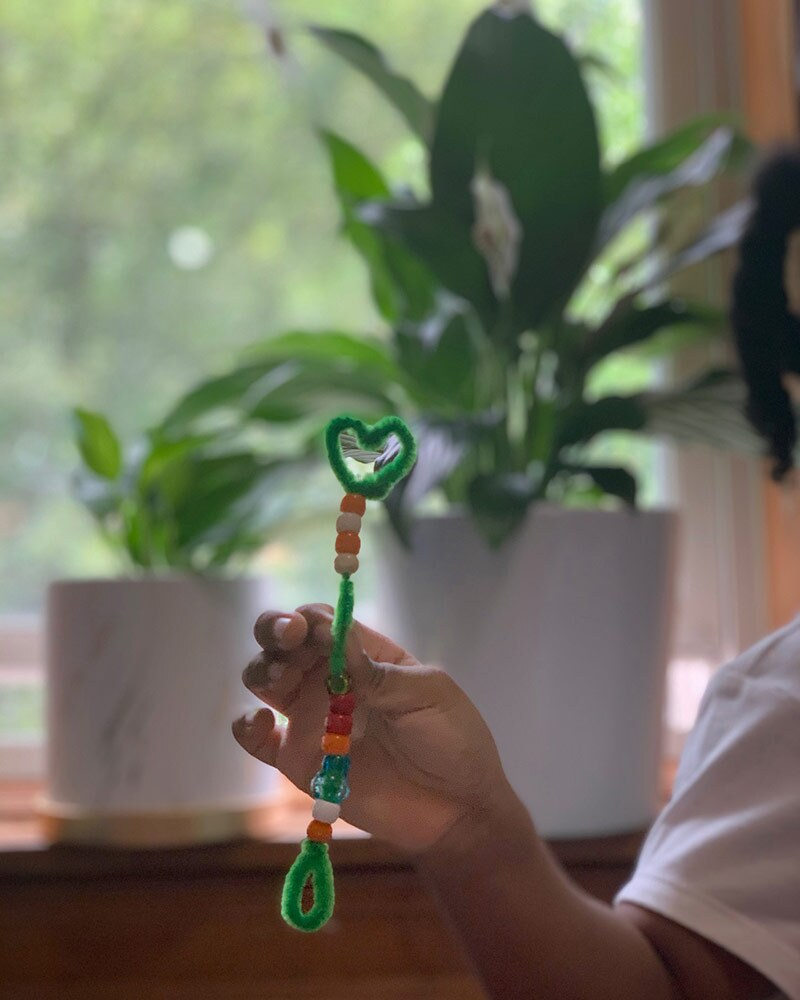 A person holds a pipe cleaner in the shape of a wand with a heart shape on top threaded with beads.