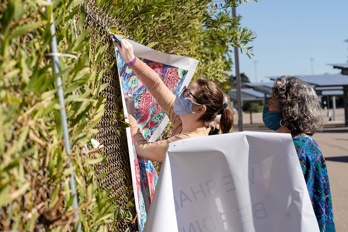 """People installing art at the """"Mesa College Drive-In: An Outdoor Art Exhibition"""" 