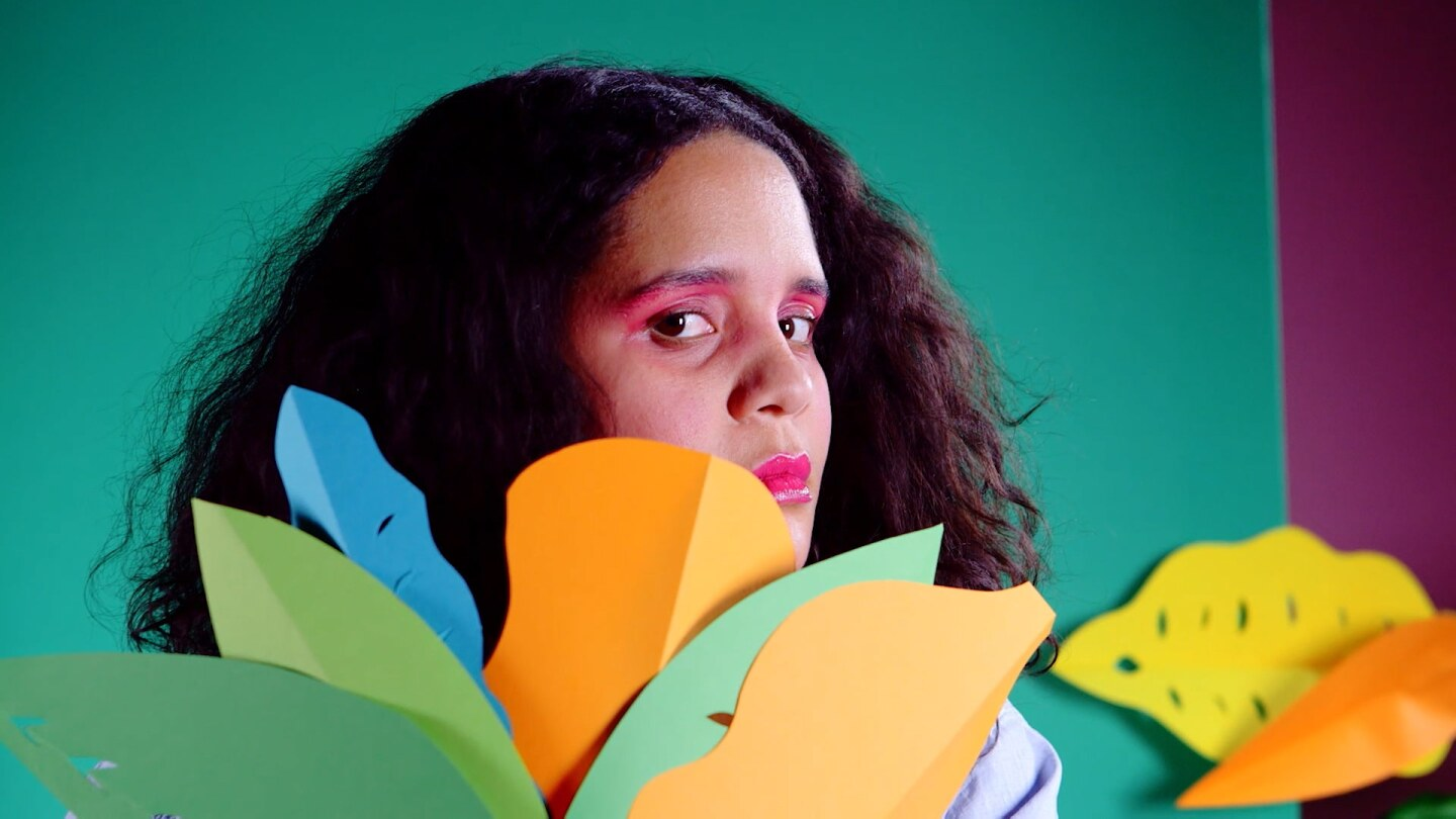Lido Pimienta appears in front of artificial foliage.