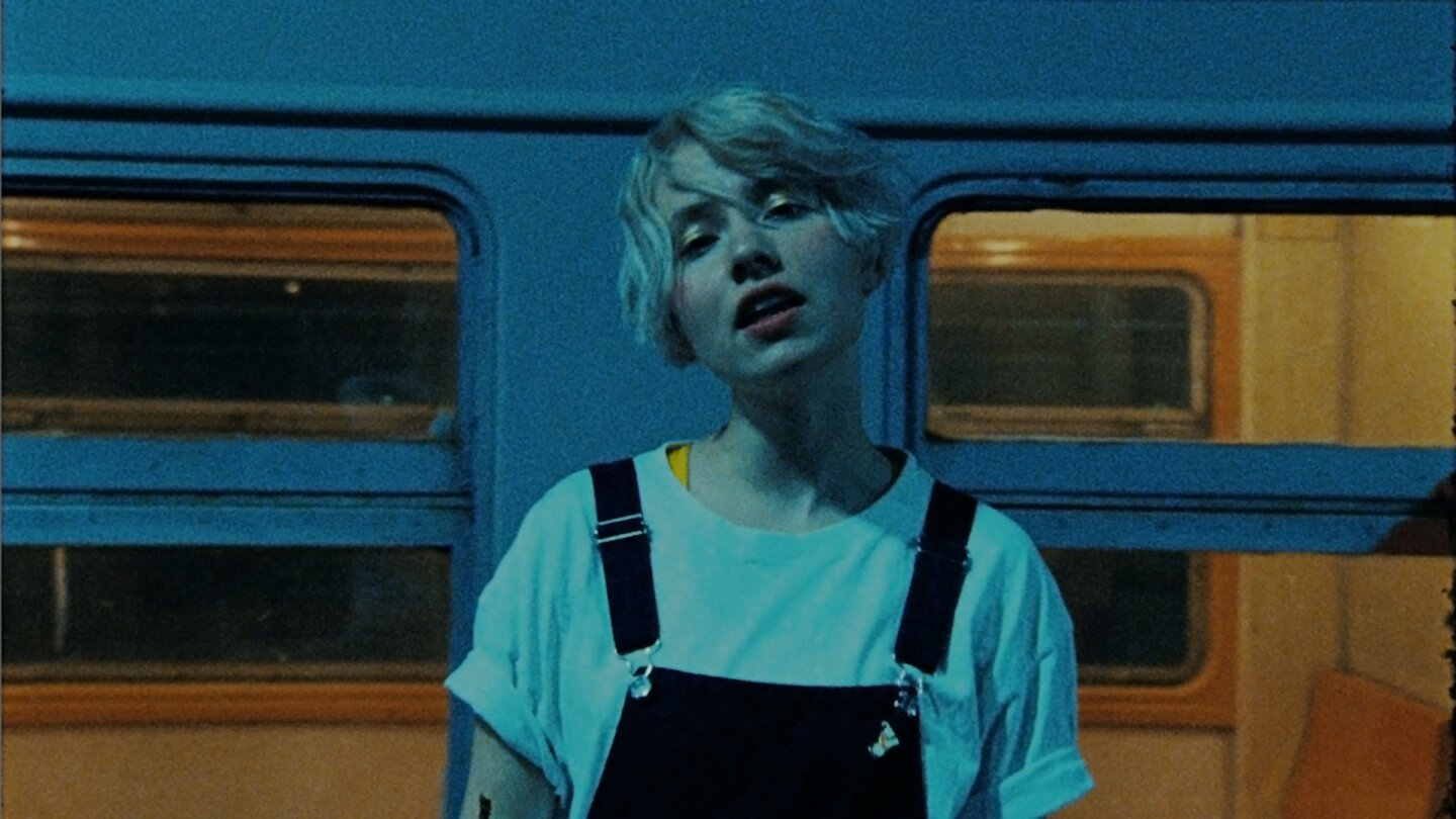 "Still from NV's ""Kata"": A woman with short hair, a white T-shirt and overalls sings in front of a train car."