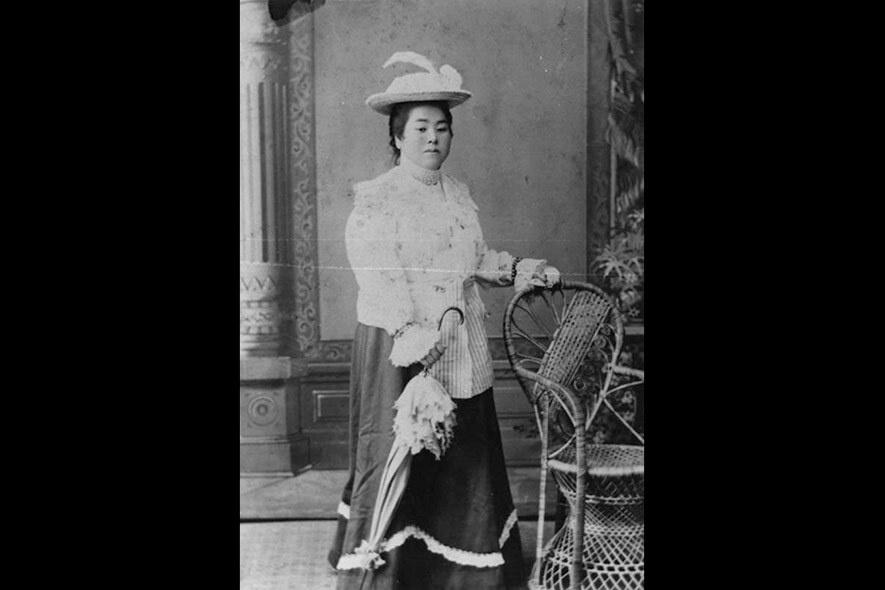 A Japanese American woman poses with a parasol for a studio portrait, circa 1900.