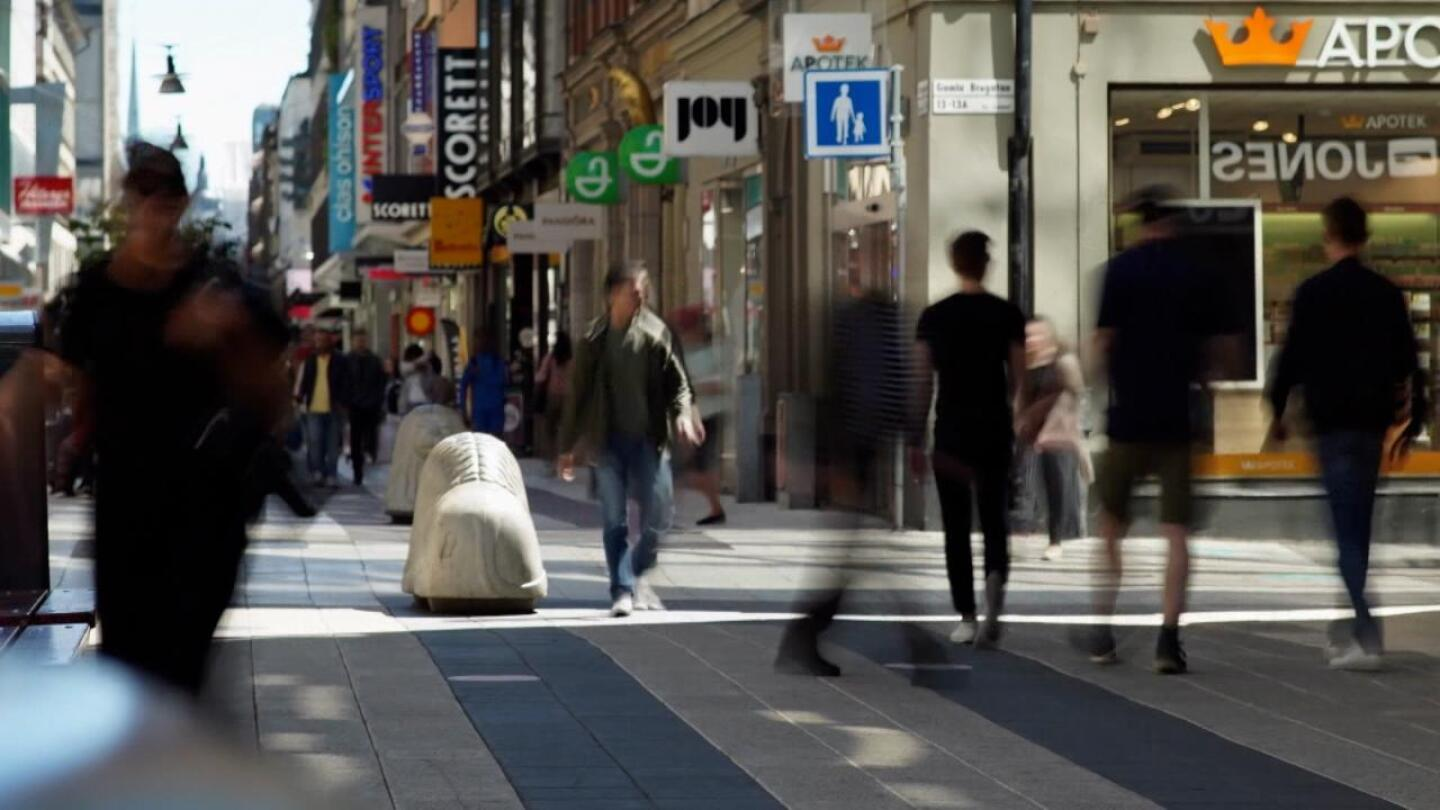 """People bustle about on a city street. 