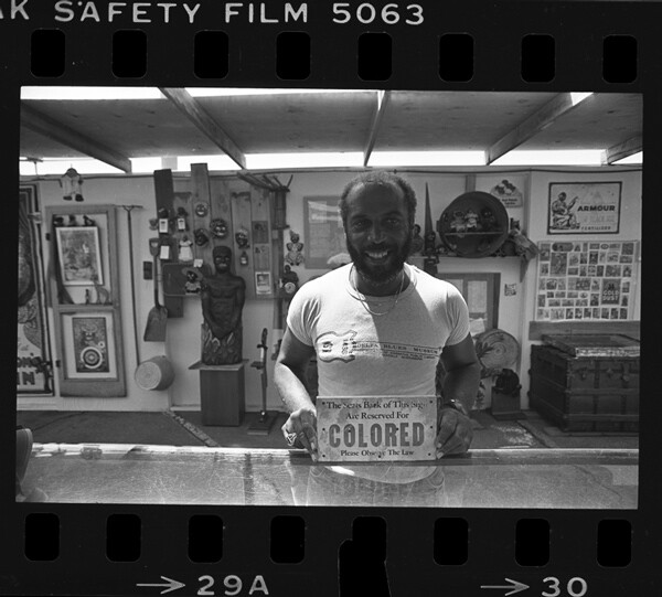 Brian Breye displaying black memorabilia at the Museum In Black, 1984. | Photo: Courtesy of UCLA Library | Digital Collections