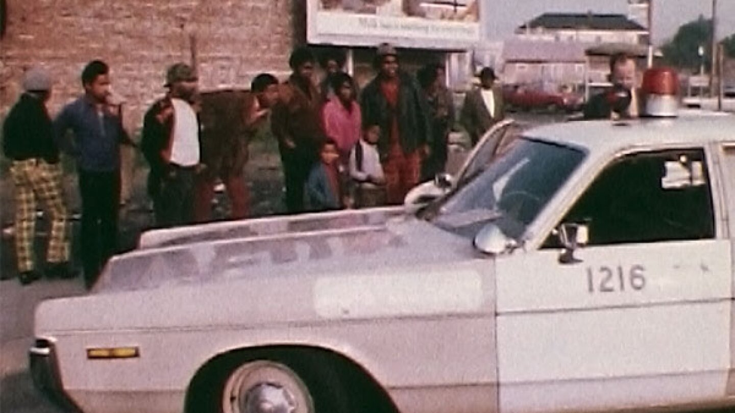 "A crowd in Oakland observes a police arrest. | Still from ""City Rising: The Informal Economy"""