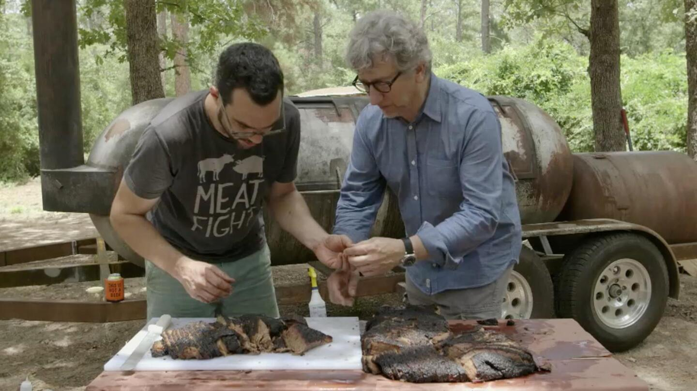 Two men prepare slabs of smoked brisket.