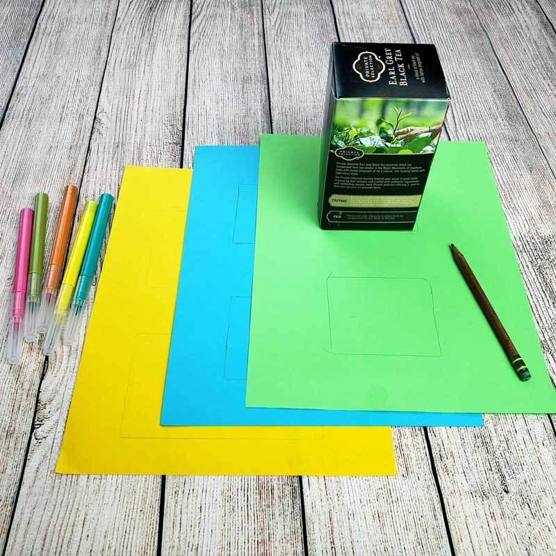 Materiales de manualidades, que incluyen una caja pequeña, marcadores y papel de construcción son colocados sobre una mesa.