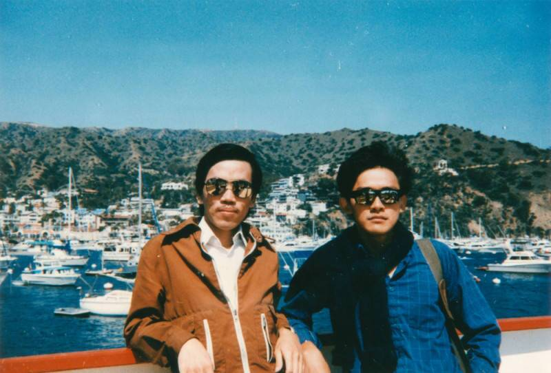 Two men in sunglasses pose next to the ocean.
