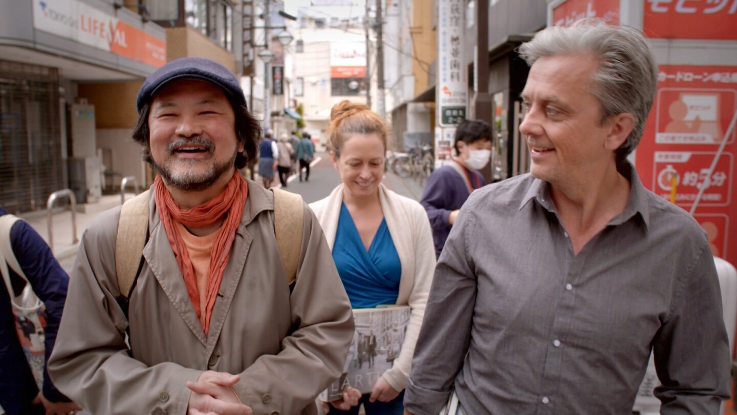 """Life-Sized City"" host Mikael Colville-Andersen walks through a small street in Japan with his smiling guide. 