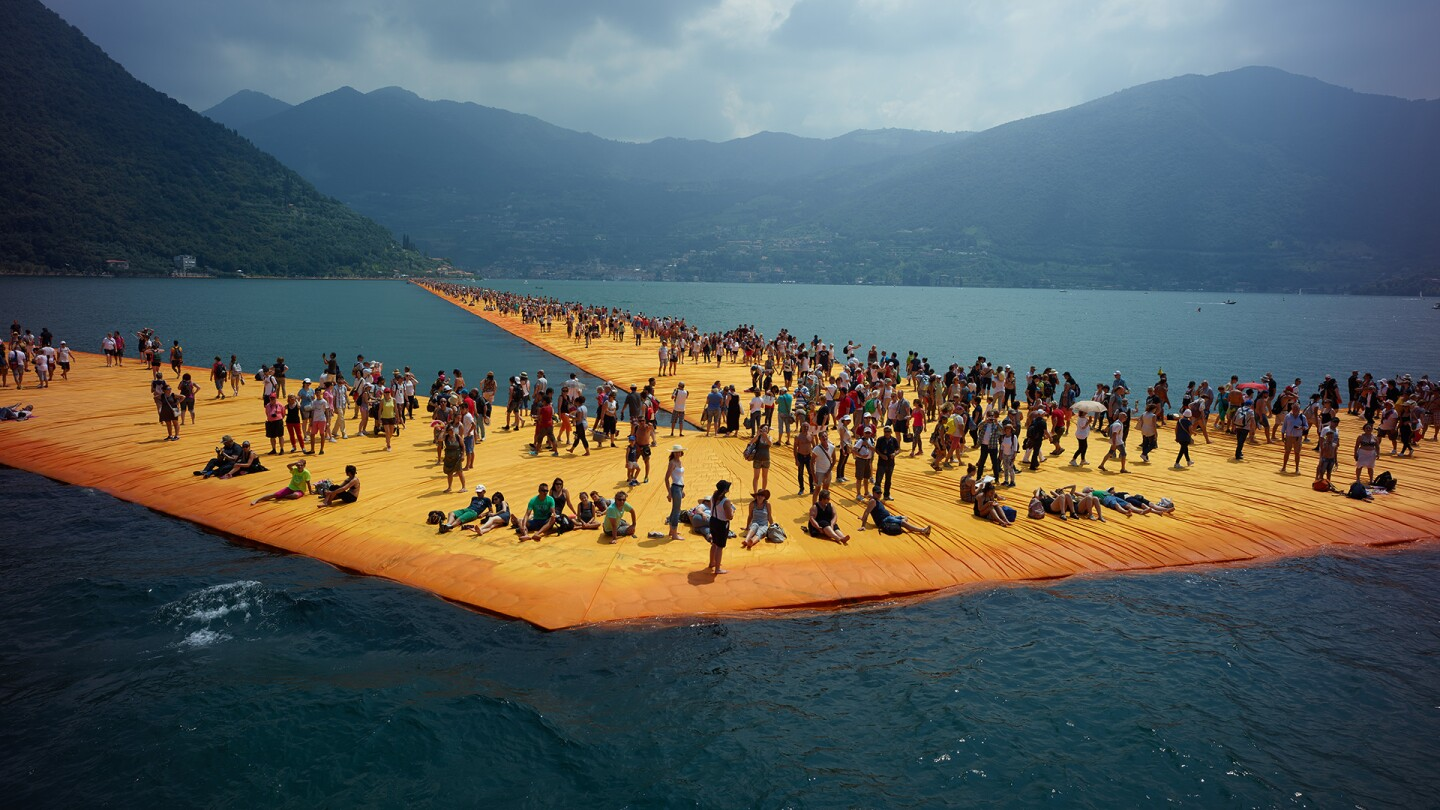 """Hundreds of people stand on artist Christo's art installation """"The Floating Piers,"""" a yellow, three kilometer walkway, on Italy's Lake Iseo. 