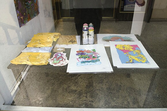 "Table display of prints from the exhibition ""Historia de Flores"" by Nestor Mondragon ""Spel"""