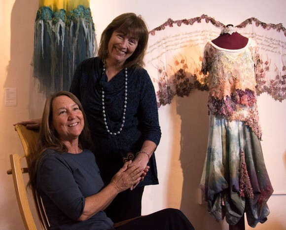 """Melinda Forbes and Julie Frankel organized the exhibition """"Earth Gowns: Narrative Dresses, Stitched Storytelling"""" at the Steynberg Gallery in San Luis Obispo. In the background is """"Rooted in Beauty"""" by Mary Wood.   Chris Daly"""