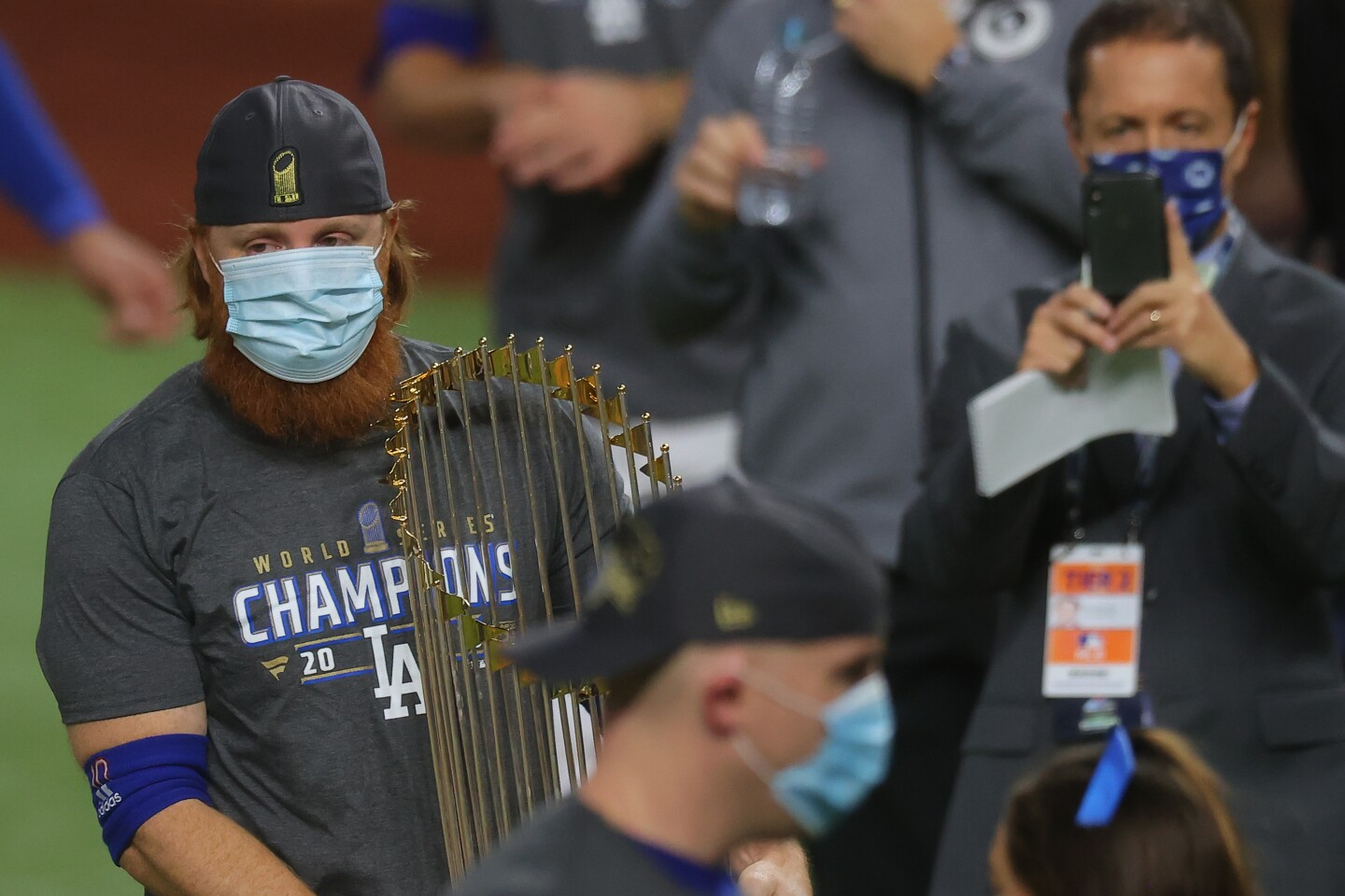 A red-headed and bearded man wearing a face mask holds a golden trophy on a baseball field.