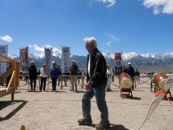 Hank Umemoto, a former Manzanar internee, walks toward the stage as banners are held up in the background representing the ten World War II internment camps and the 442nd Regimental Combat Unit