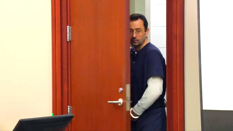 Larry Nassar walking through a door in handcuffs. | Democracy Now