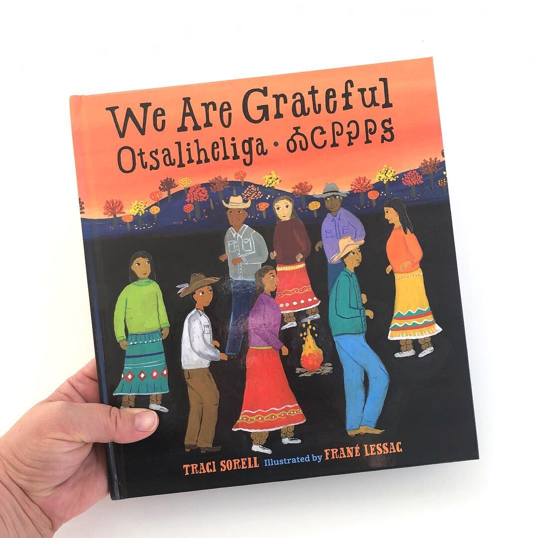 """Book cover of """"We Are Grateful: Otsaliheliga"""" by Traci Sorell and illustrated by Frané Lessac featuring colorful illustrations of people"""