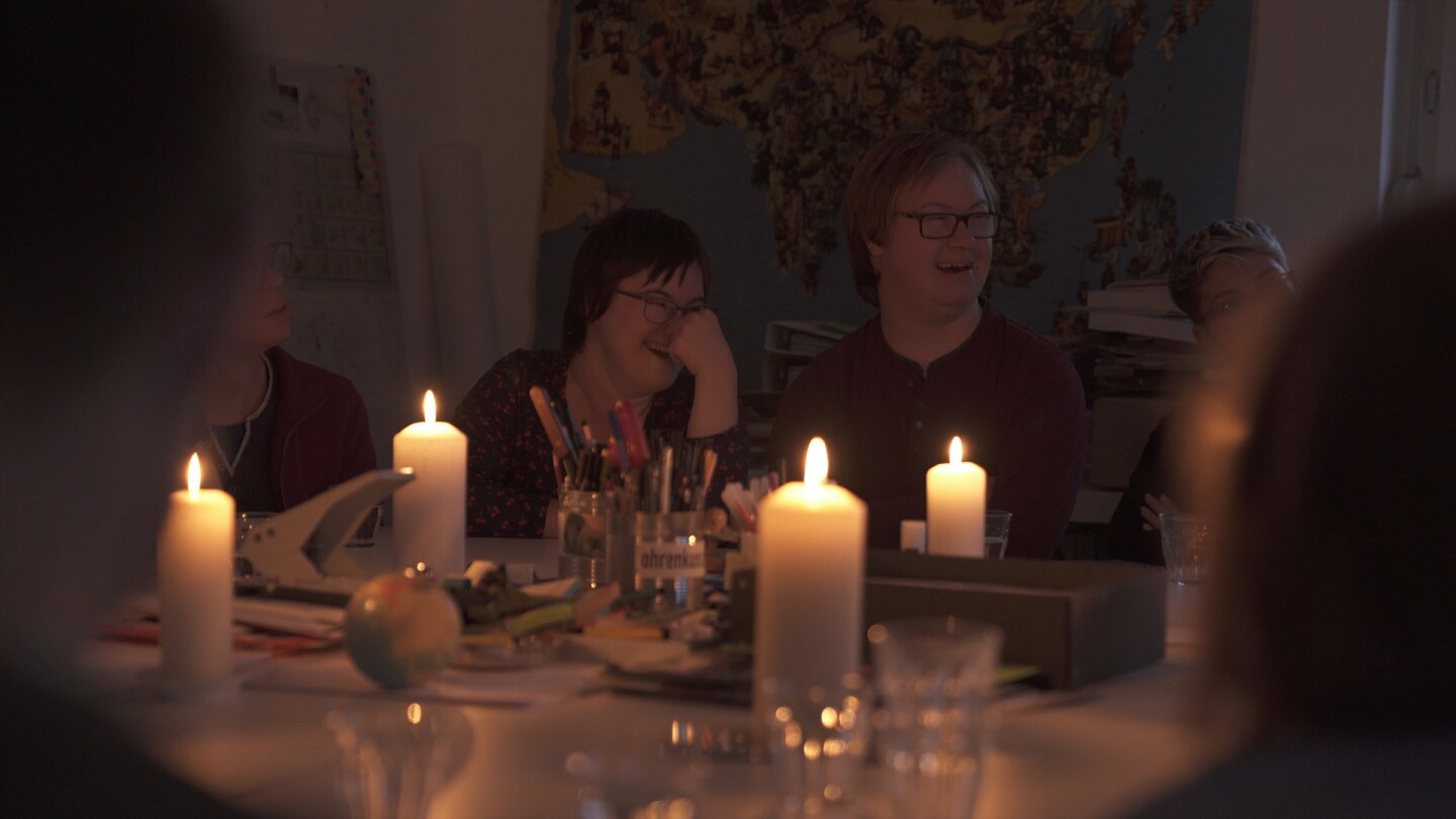 "Two youths with Down Syndrome talk with candlelight in a still from ""Nothing Down About It."" 