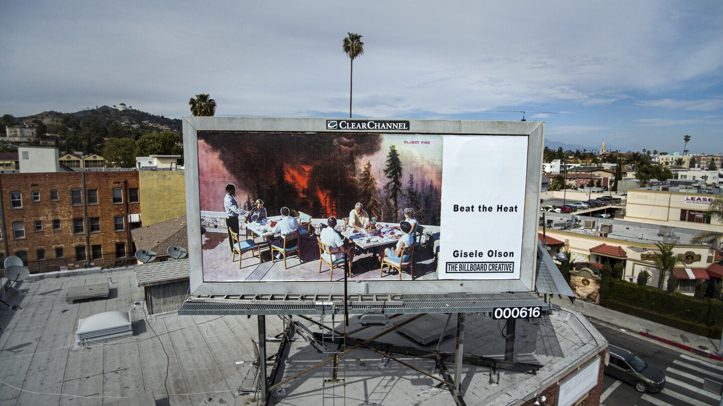 Artist Gisele Olson's billboard located near the intersection of Hollywood Blvd. and Normandie Ave. alters vintage postcards to create new narratives that dismantle the materials' nostalgic, comfortable perception of the U.S., using collage to critique and reinterpret America's idyllic self-image.