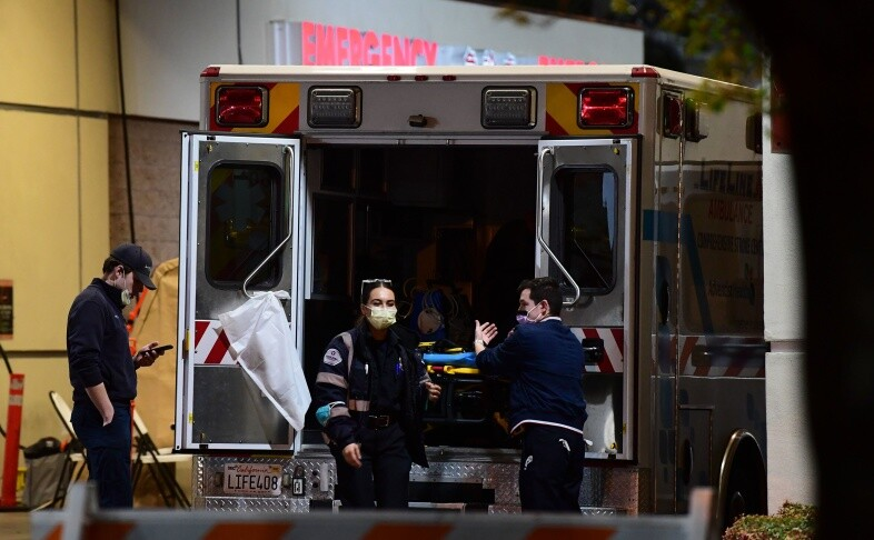 Paramedics wearing facemasks work behind an ambulance at the Garfield Medical Center in Monterey Park on March 19, 2020. | Frederic J. Brown/AFP/Getty Images
