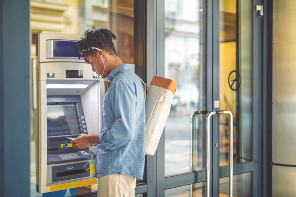 Man wearing a backpack making an ATM transaction.   iStock