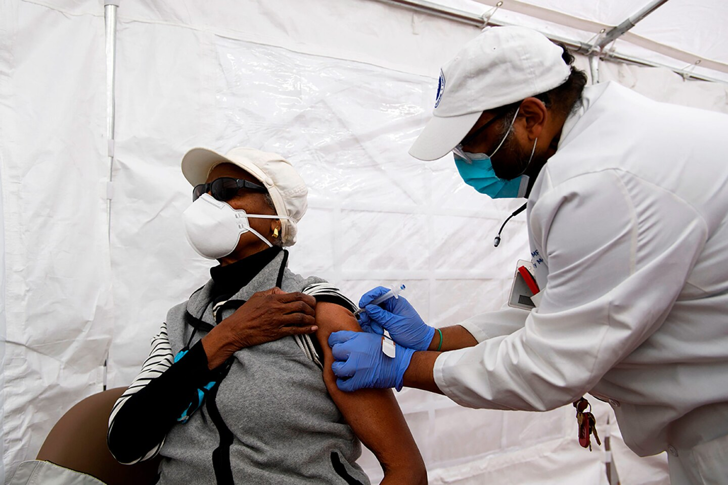 Dr. Jerry P. Abraham administers a COVID-19 vaccination to a senior citizen in a vaccination tent at the Kedren Community Health Center on January 25, 2021 in Los Angeles, California.