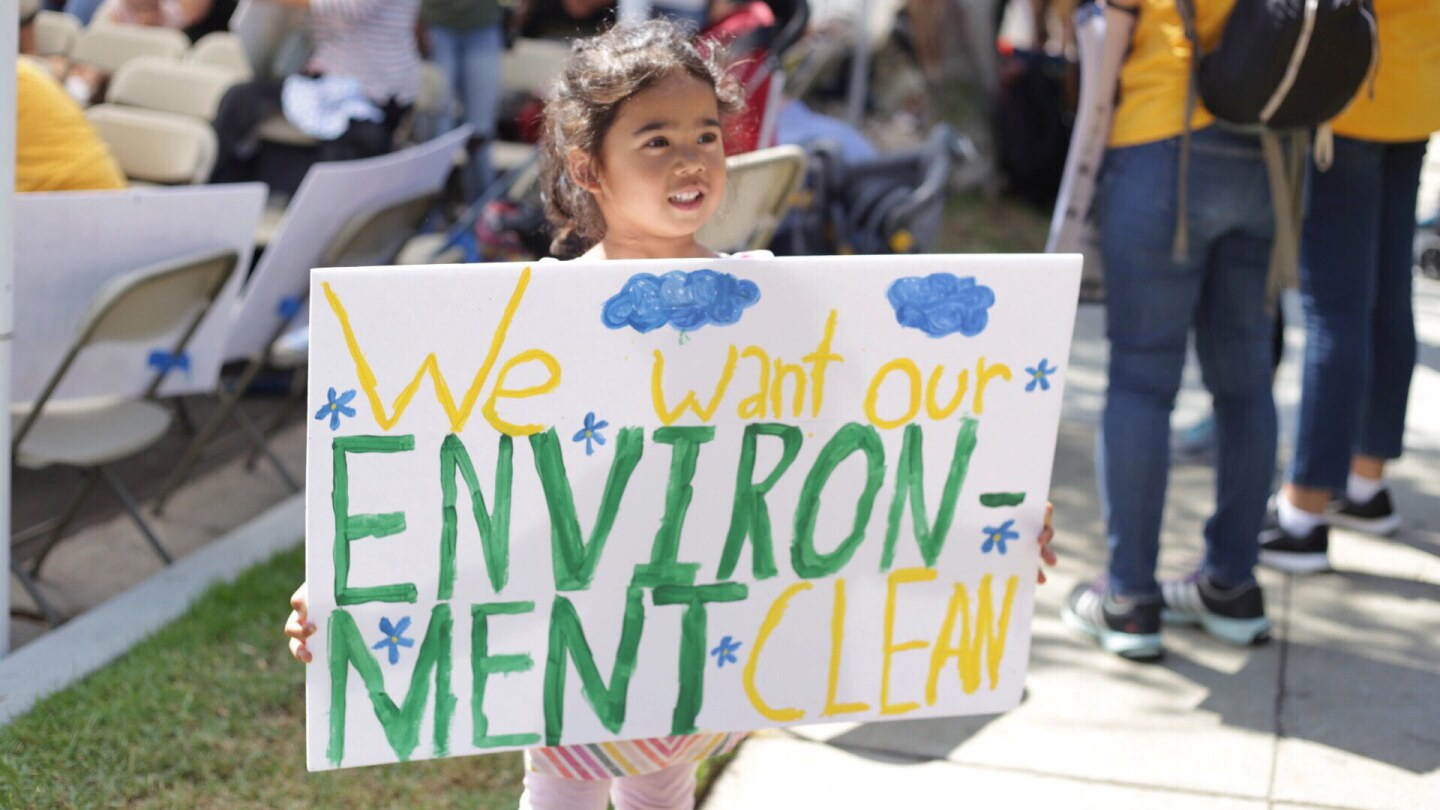 "A small child holds a sign up at a protest. It reads ""We want our ENVIRONMENT CLEAN."""