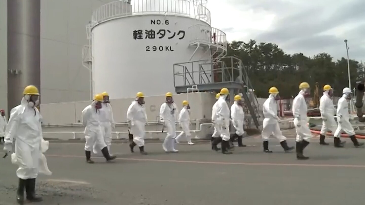 Workers in uniform wearing gas masks walk through a nuclear power plant facility.