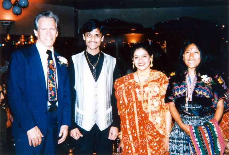 A bride and groom in traditional Indian dress pose with a man and a woman.