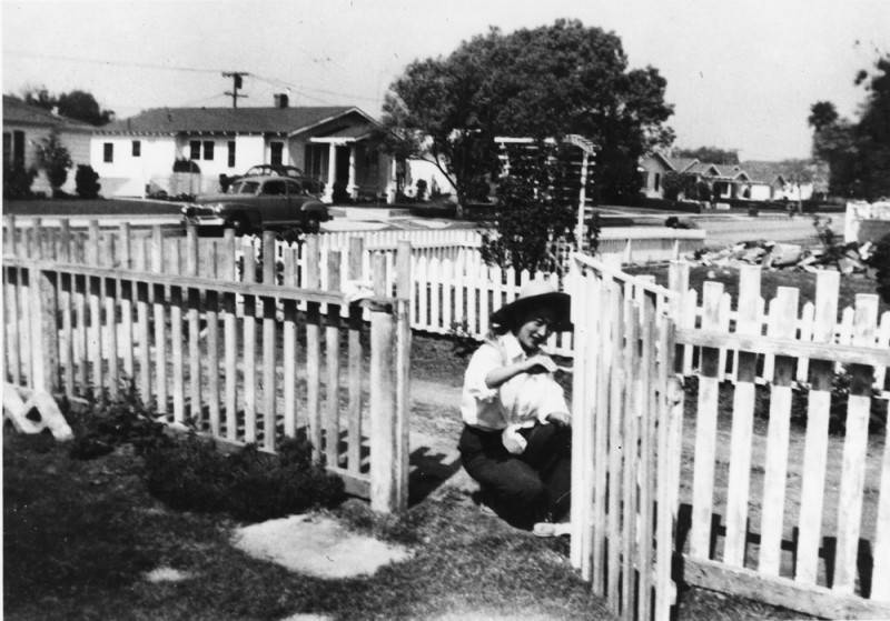Black and white photo of a Japanese American woman painting a picket fence in the backyard of a home in West Los Angeles, circa 1950