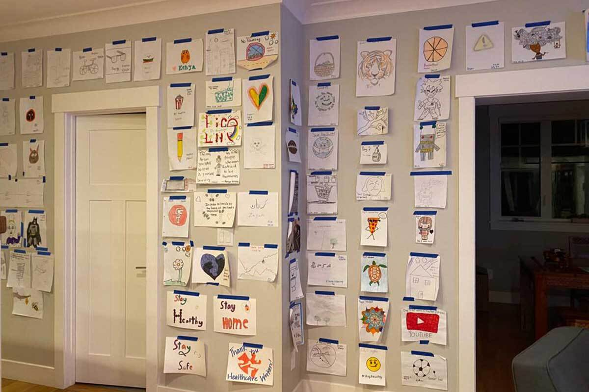 A white wall inside a home is covered in children's artwork.
