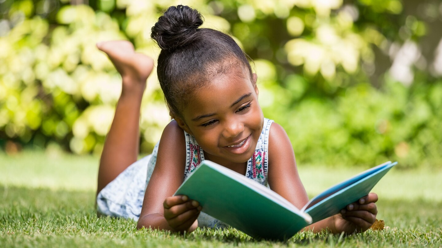 A small child smiles as she reads a book in a grassy place.
