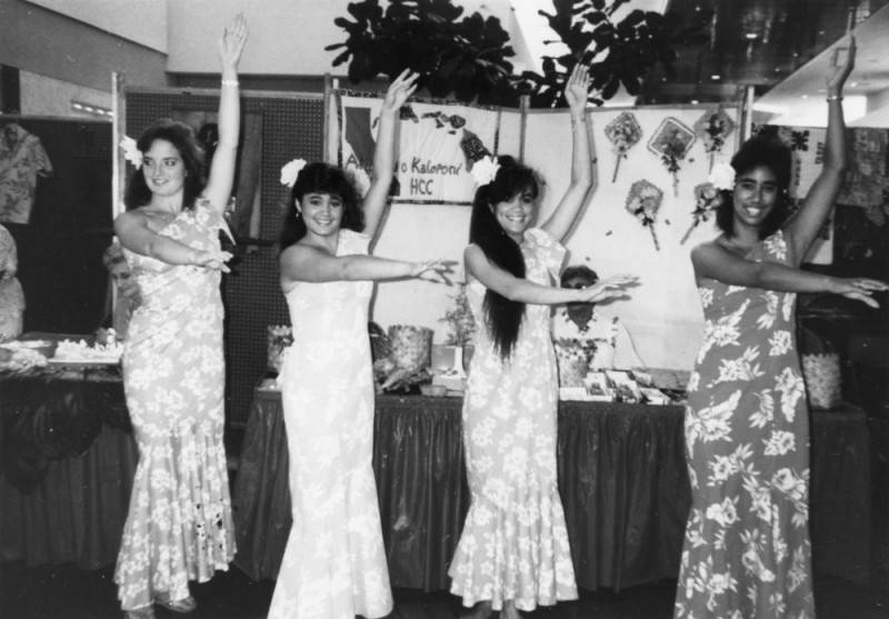 Black and white photo of four women in Hawaiian dresses performing a Hawaiian dance, 1987.